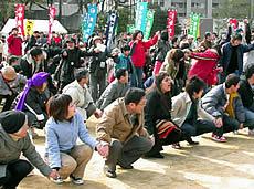 「平和への大きな波を起こそう」。手をつなぎウエーブする「ピース・フェスタ」の参加者=神戸市???区、東遊園地
